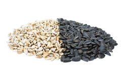 Some black and shelled roasted sunflower seeds. Isolated on the white background Royalty Free Stock Photos