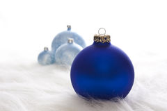 Some blue christmas baubles. Arrangement of some blue christmas baubles on white fur Stock Image