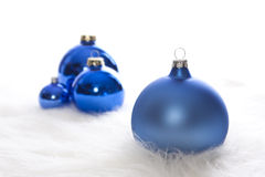 Some blue matt and shiny christmas baubles. Arrangement of some blue matt and shiny christmas baubles on white fur Royalty Free Stock Photo