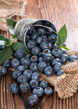Some Blueberries in a small Bucket. On wooden background (macro shot Stock Photos