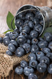 Some Blueberries in a small Bucket. On wooden background (macro shot Royalty Free Stock Photo