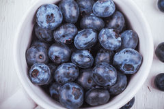 Some blueberries in white cup. Top view on handful of ripe and fresh blueberries in white cup Royalty Free Stock Images