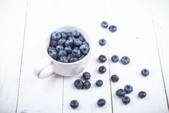 Some blueberries in white cup. View from above on handful of ripe and fresh blueberries in white cup Stock Photos