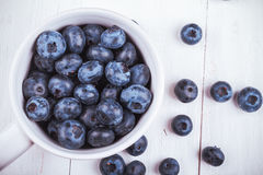Some blueberries in white cup. View from above on handful of ripe and fresh blueberries in white cup Royalty Free Stock Image