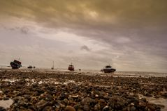 Some boats on the beach of east England. Before the tide stock image