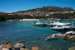 Some boats moored in Porto Cervo`s marina. View of some boats moored in Porto Cervo`s marina between plants and luxury buildings in a blue sea Royalty Free Stock Photography