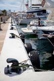 Some boats moored to black bollards in a marina on an island in the Mediterranean Sea royalty free stock images