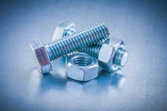 Some bolts and screw nuts on metallic background. Construction concept Stock Photo