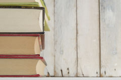 Some books on a shelf. White wooden background. Stock Photo