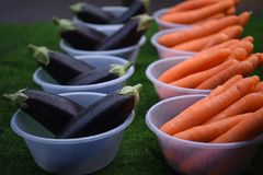 Bowls filled with fresh vegetables of carrots and aubergines. Some bowls filled with fresh veg with bright orange color carrots and dark ripe aubergines. Ready royalty free stock photo