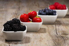 Some bowls filled with wild berries. On wooden background blackberries in front Stock Photo
