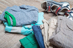 Some boy's casual outfits in stack. Boy's casual outfits on wood board background royalty free stock image