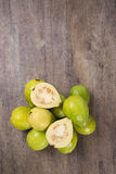Some brazilian guavas over a striped surface. Some brazilian guavas over a wooden background. Fresh fruits royalty free stock photography