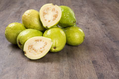 Some brazilian guavas over a striped surface. Some brazilian guavas over a wooden background. Fresh fruits stock photos