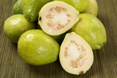 Some brazilian guavas over a striped surface. Some brazilian guavas over a wooden background. Fresh fruits stock image