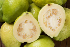 Some brazilian guavas over a striped surface. Some brazilian guavas over a wooden background. Fresh fruits stock photography