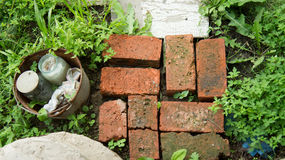 Some bricks and bucket on a grass. Real estate traces stock image