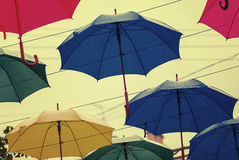 Some bright umbrellas in a rainy day. Interesting positive bright photo of a few colorful (red, blue, yellow, green) full size manual umbrellas floating in the royalty free stock images