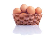 Some brown eggs in a basket isolated on a white background with. Some brown eggs in basket isolated on a white background with reflection side view stock photos