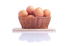 Some brown eggs in a basket on a small cutting board isolated on. Some brown eggs in basket on small cutting board isolated on white background with reflection royalty free stock photography