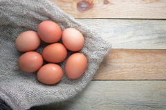 Some brown eggs on a sackcloth. On a wooden table Stock Photos
