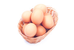 Some brown eggs in a wicker basket isolated on white background. Some brown eggs  wicker basket isolated on white background with shadow top view and side view Stock Photo