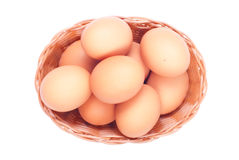 Some brown eggs in a wicker basket isolated on white background. Some brown eggs in wicker basket isolated on white background top view Royalty Free Stock Image