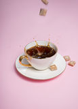 Some brown sugar cubes droppin into coffee cup. Some brown sugar cubes droppin into white  coffee cup on pink background Royalty Free Stock Photos