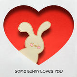 Some bunny loves you. Creative concept photo of a bunny in a heart made of paper on white background Royalty Free Stock Photo