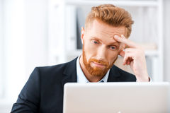 Some business troubles. Frustrated bearded businessman working on laptop and touching his head while sitting at his working place Royalty Free Stock Photography