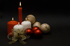 Some candles and golden bonds and balls. Christmas card with some candles and golden bonds and balls on a black background Royalty Free Stock Images