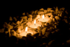 Some candles with stones. On black background Stock Image