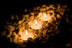 Some candles with stones. On black background Stock Photos