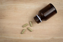 Some capsule and the empty bottle. On the wood block stock photography