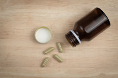 Some capsule and the empty bottle. On the wood block stock image