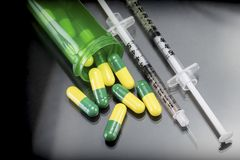 Some capsules green and yellow out of a boat together with syringes Stock Photo