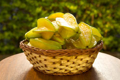 Some caramboles in a basket over a wooden surface. Fresh fruit Royalty Free Stock Image