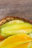 Some caramboles in a basket over a wooden surface. Fresh fruit Royalty Free Stock Photo