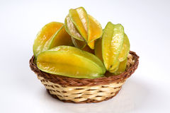 Some caramboles in a basket over a wooden surface. Fresh fruit Stock Images
