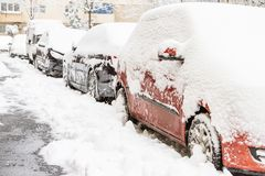 Some cars covered with snow after a storm. Cars covered with snow after a storm Stock Images
