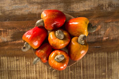 Some cashew fruit over a wooden surface. Some cashew fruit over a wooden surface Royalty Free Stock Photography