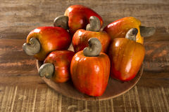 Some cashew fruit over a wooden surface. Some cashew fruit over a wooden surface Royalty Free Stock Photos