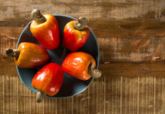 Some cashew fruit over a wooden surface. Some cashew fruit over a wooden surface Stock Image