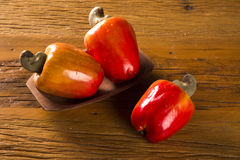 Some cashew fruit over a wooden surface.  Stock Photo