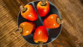 Some cashew fruit over a wooden surface. Some cashew fruit over a wooden surface Royalty Free Stock Photo