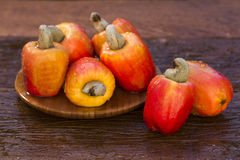 Some cashew fruit over a wooden surface. Some cashew fruit over a wooden surface Stock Photography