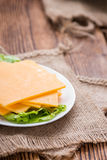 Some Cheddar Slices. (close-up shot) on vintage wooden background Royalty Free Stock Image