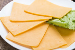 Some Cheddar Slices. (close-up shot) on vintage wooden background Royalty Free Stock Photography