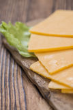 Some Cheddar Slices. (close-up shot) on vintage wooden background royalty free stock photos
