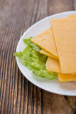 Some Cheddar Slices. (close-up shot) on vintage wooden background Royalty Free Stock Photo